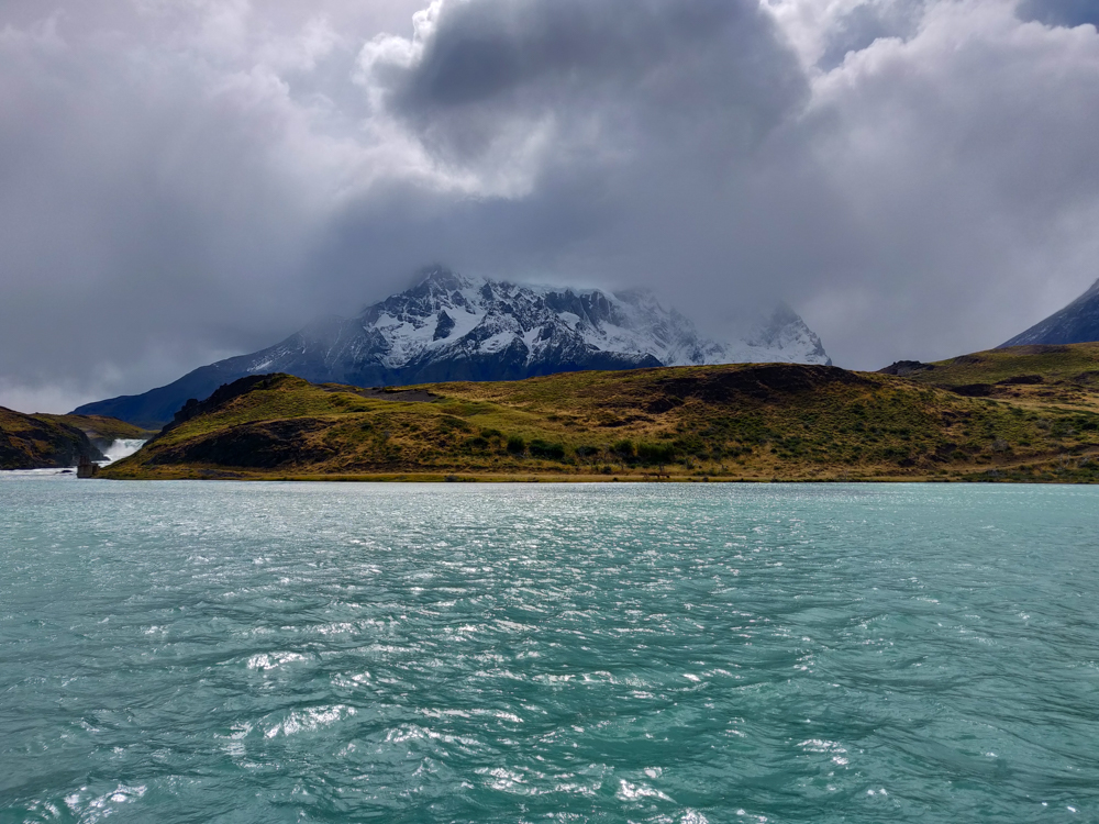 Crazy blue water with cloudy mountains in the background