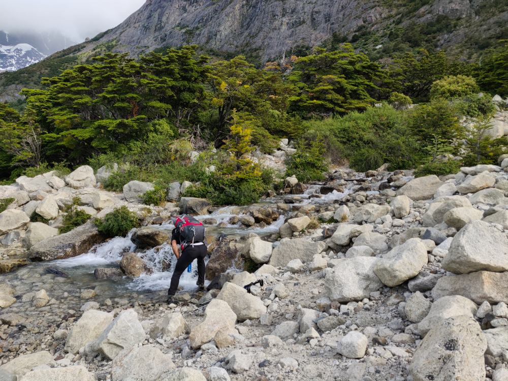 Mike filling his water from a rocky stream