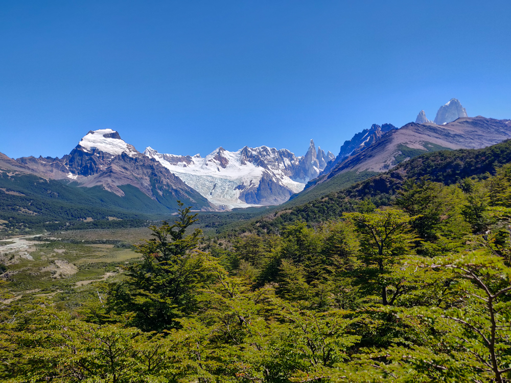 Green landscape with mountains and a glacier in the distance