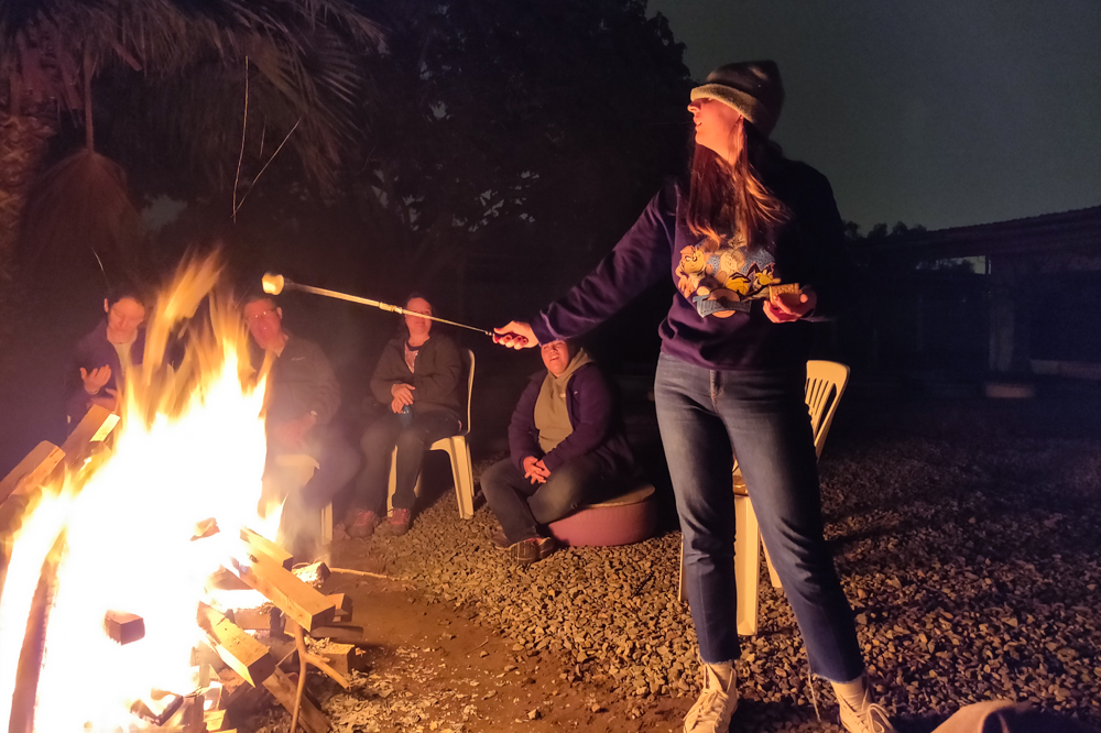 Julie toasting a marshmallow with her hat pulled over her eyes